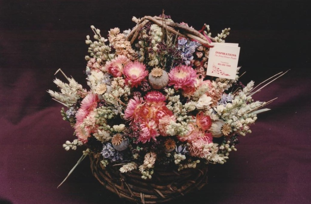 basket of pink flowers with label saying inspirations - the dried flower people
