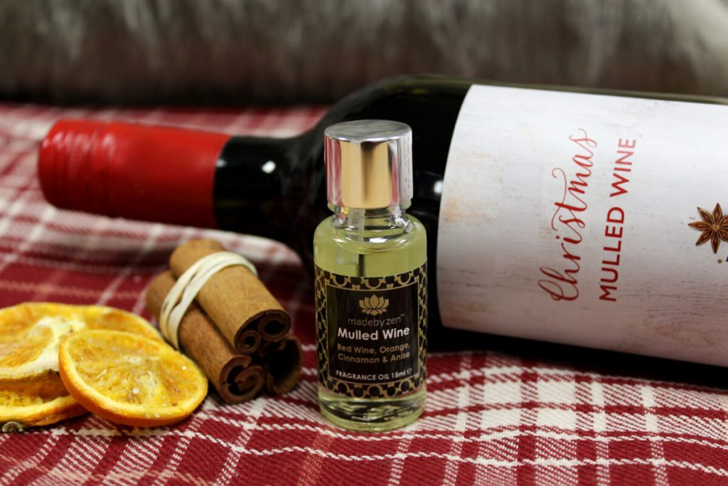 MadebyZen Mulled Wine fragrance oil on table with wine and spices