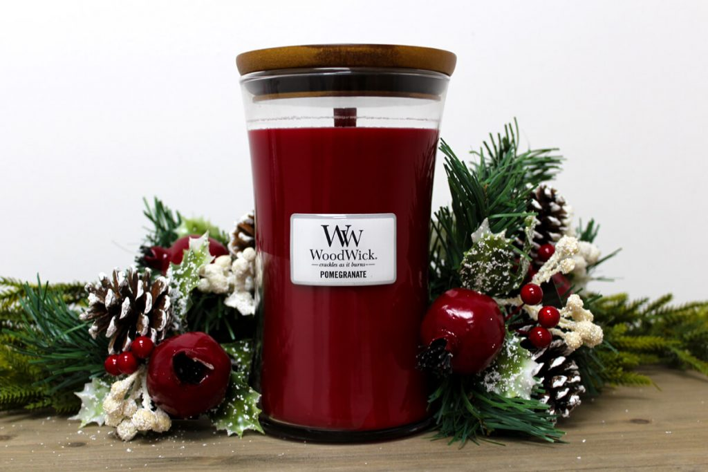 Woodwick Pomegranate Scented Candle next to Christmas decorations