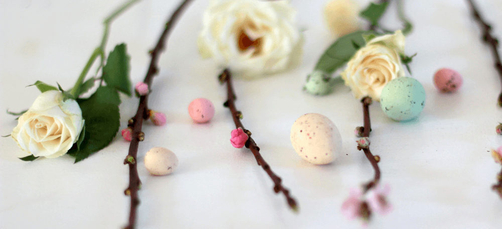 White rose buds, blossom branches and speckled eggs in pastel colours on an easter table
