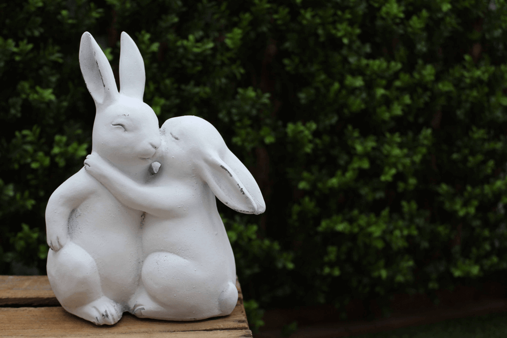 two white easter bunny ornaments hugging on table outside