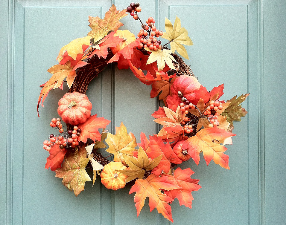 autumn wreath hanging on doors with pumpkins, berries and red leaves