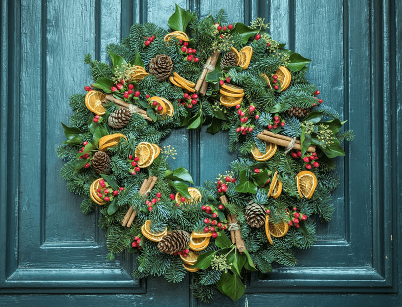 christmas wreath with cinnamon, berries, orange and pine cones hanging on teal door