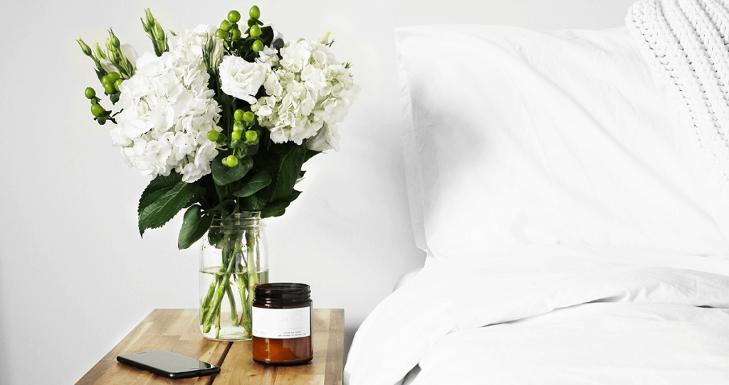 soft neutral flowers in a vase next to a bed