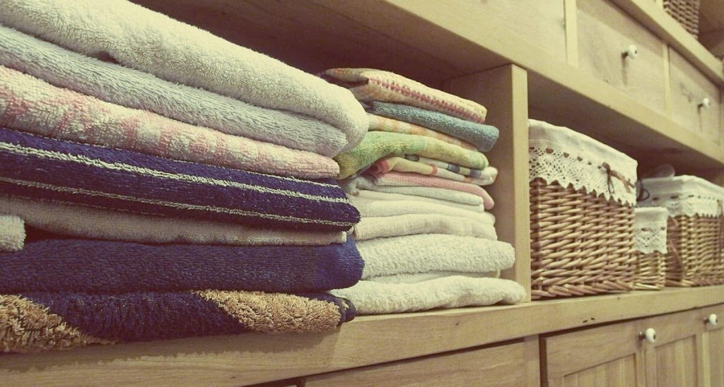 cupboard shelves with towels and baskets