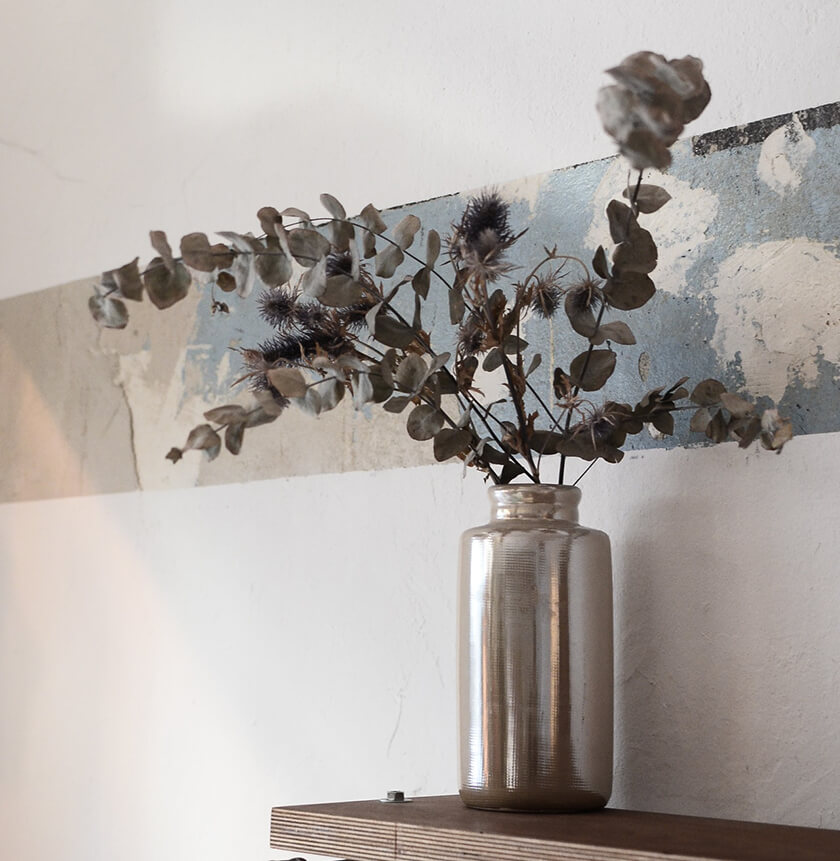 dried eucalyptus stems and dried flowers in vase on shelf