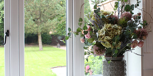 Artificial Flowers bouquet of faux hydrangeas and roses in vase on windowsill