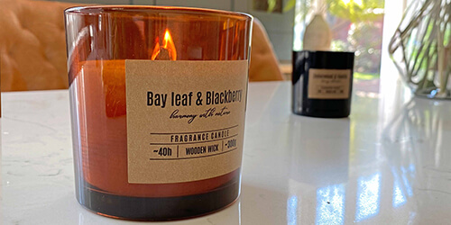 Candles and home fragrance - two lit ivory church candles next to plant